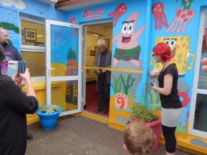 Mr Eamonn Barrett cuts the yellow ribbon to officially open the mural at Piercestown NS